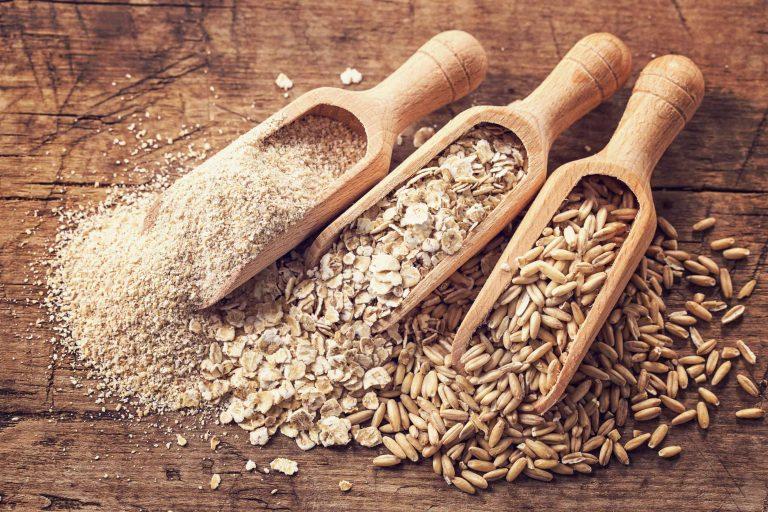 Haferflocken, Kleie und Samen in Holzlöffeln