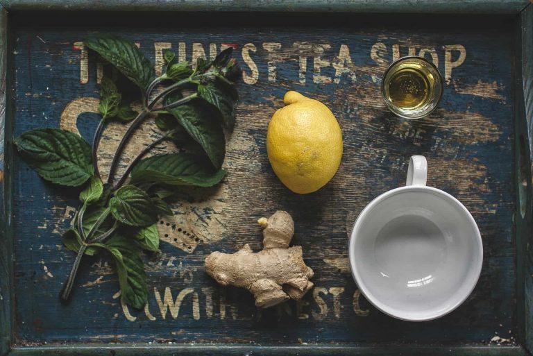 Minze, Zitrone, Ingwer, Honig und eine Tasse mit Wasser auf einem Brett