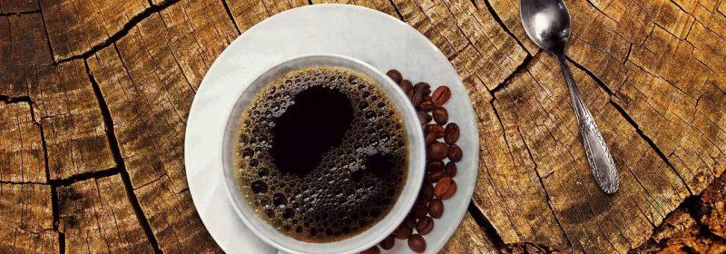 Tasse mit Filterkaffee und Bohnen auf Holztisch