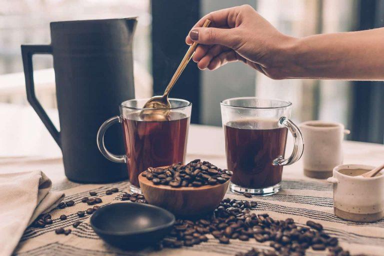 Kaffeegläser, Bohnen und Kanne auf Tisch
