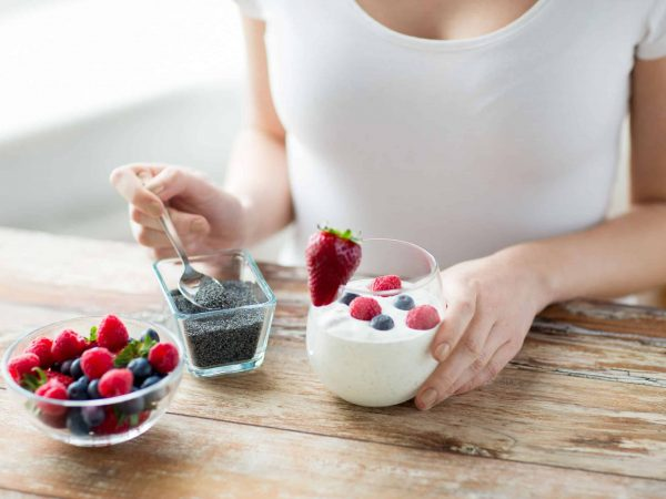 healthy eating, vegetarian food, diet and people concept – close up of woman hands with yogurt, berries and poppy or chia seeds on spoon