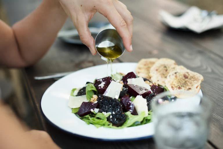 Öl wird über einen bunten Salat gegossen
