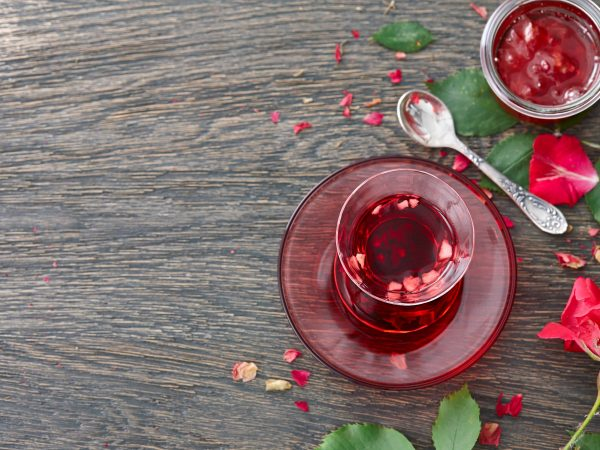 Food background with a glass turkish cup of hibiscus tea with fruit pieces, rose jam and rose flower on a dark wooden background.