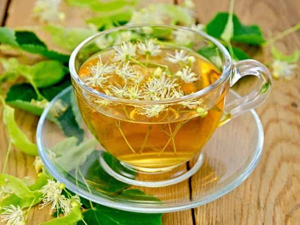 Herbal tea in a glass cup, fresh linden flowers on a background of wooden boards