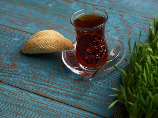 National Azerbaijan pastry shekerbura with nuts and honey and glass of black tea on wooden table with wheat grass semeni,background, close up. Novruz holiday dessert