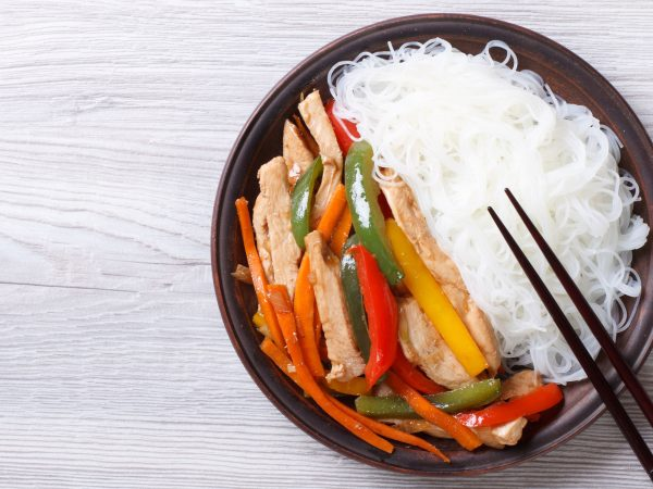 Rice noodles with chicken and vegetables close-up on the table. horizontal view from above