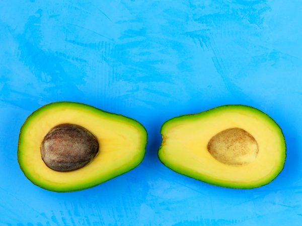 Avocado cut in half, one slice with core on a light turquoise surface, close-up. Delicious and nutritious fruit, image with copy space.